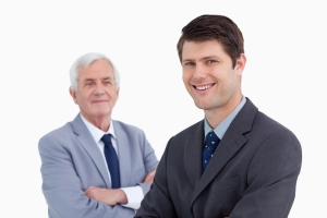 A mentor stands behind a protege as part of succession planning