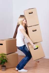 A woman moves boxes as part of her job relocation