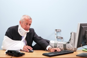 A man in casts at a desk reflecting bad ergonomic office design