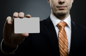 A man holds up a card as proof of his many professional designations