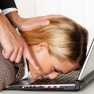 A woman's face is pressed to her keyboard in a representation of workplace bullying