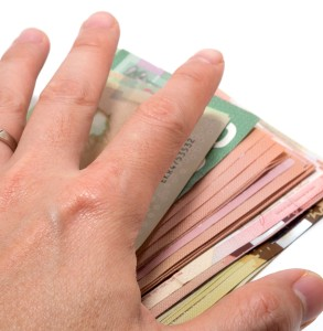 A hand grasping money from a small business owner instead of total compensation