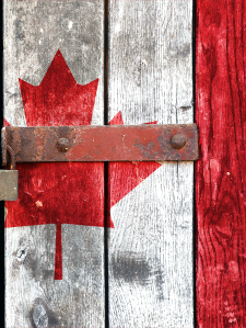 A Canadian flag painted on a locked gate symbolizing the struggles of Canadian citizenship and immigration
