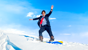 Man in business suit snowboarding, representing Olympian employees