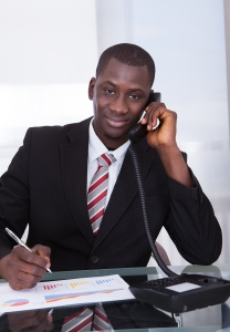 A man sits at a desk conducting a phone interview