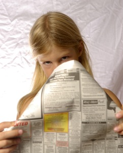 Young girl peering disdainfully over classified ads