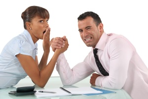 A woman yawns as she arm wrestles a man
