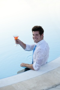 A business man holds a drink in a pool
