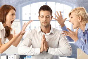 A man stands zen between two fighting coworkers illustrating good leadership skills