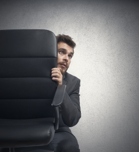 A man hides behind his desk chair because of making mistakes at work