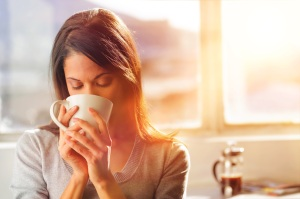 A woman drinks coffee on her first day of work