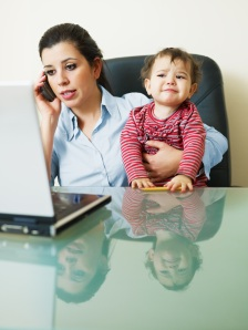 A sandwich generation mom requiring performance management works while holding a baby