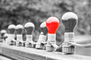 A red light bulb stands out among grey ones representing thought leadership among recruitment agencies.