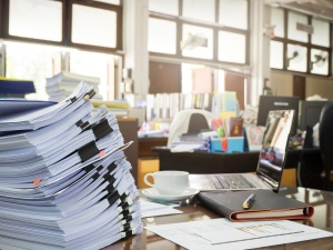 Cluttered desk with large stack of papers in foreground
