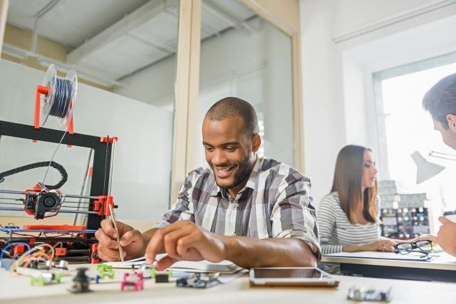 Man at desk with 3D printer