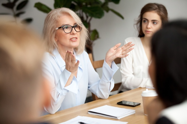 Woman speaking while seated at boardroom table