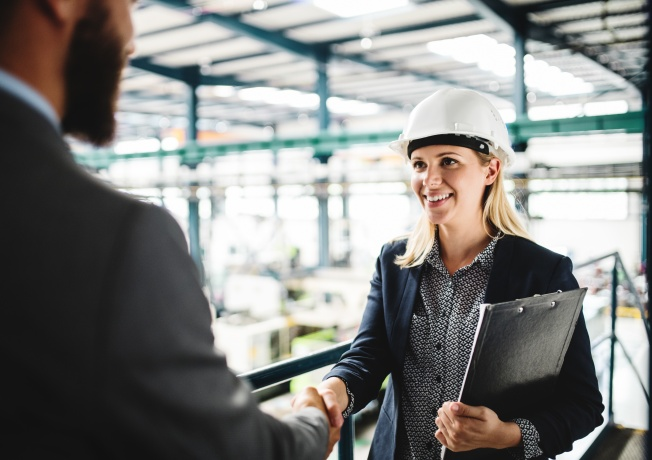 Woman in hard hat shaking hands with man in suit