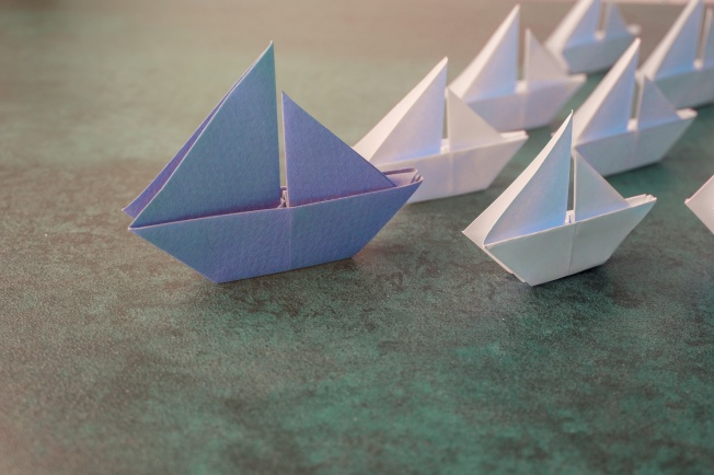 Origami paper sailboats, leadership business concept