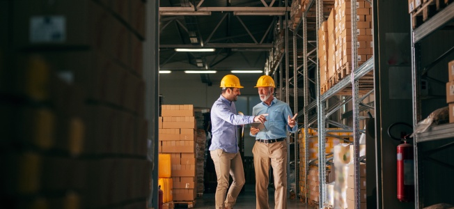 Workers walking in storage and pointing at boxes: workplace health and safety