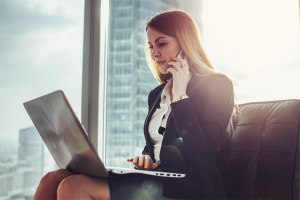 Young woman waiting in a hall sitting in modern office: how to follow up after an interview