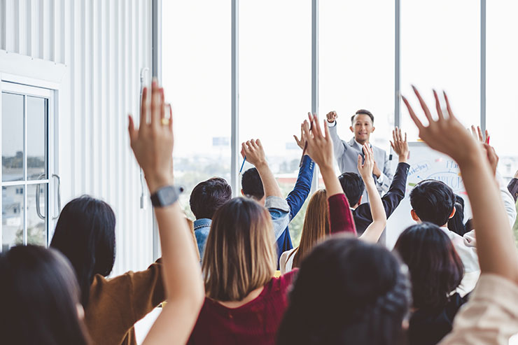 Outdoor team building ideas: business people raising their hands