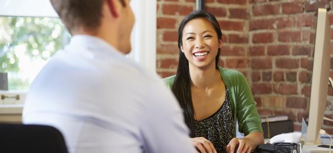 Smiling woman at desk speaking to man