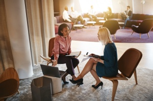 Negotiating a job offer: Two businesswomen discussing work on a laptop in an office