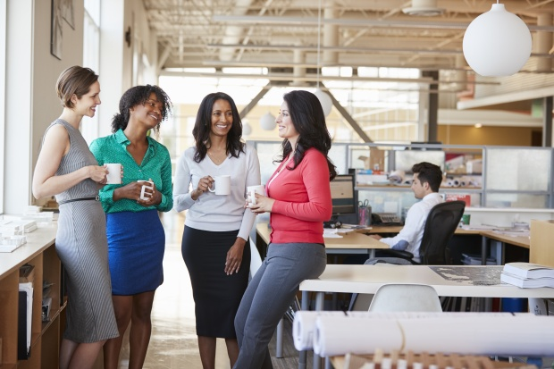 Managing millennials in the workplace: Work colleagues chatting over coffee in the office